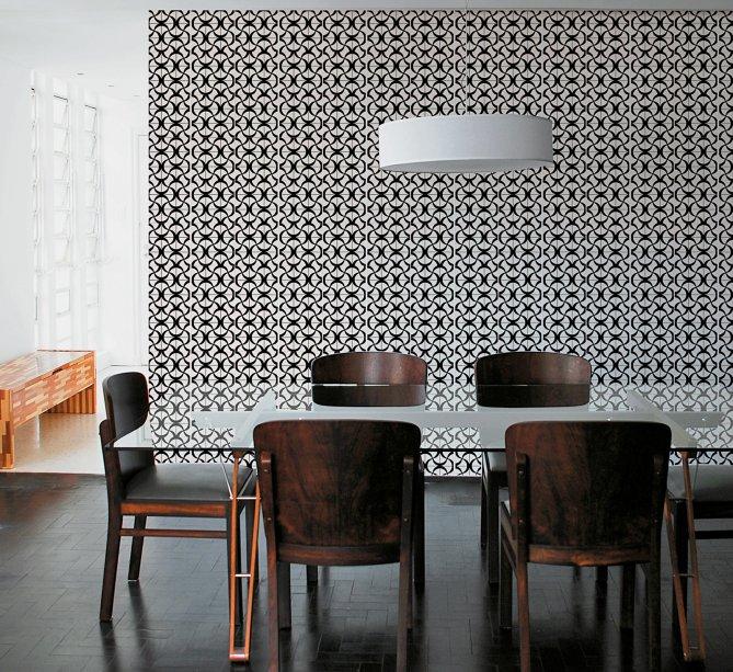 Sala de jantar com parede recoberta por azulejos monocromáticos assinados pela Pavão Revestimentos, projeto da arquiteta Carine Canavesi.
