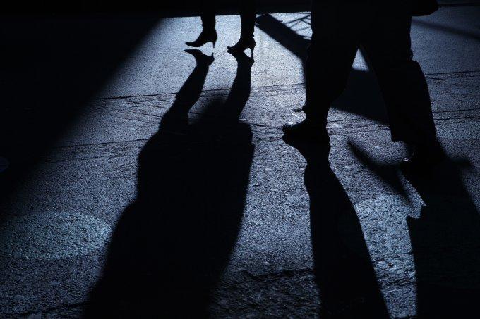 Male following female into blue night shadows