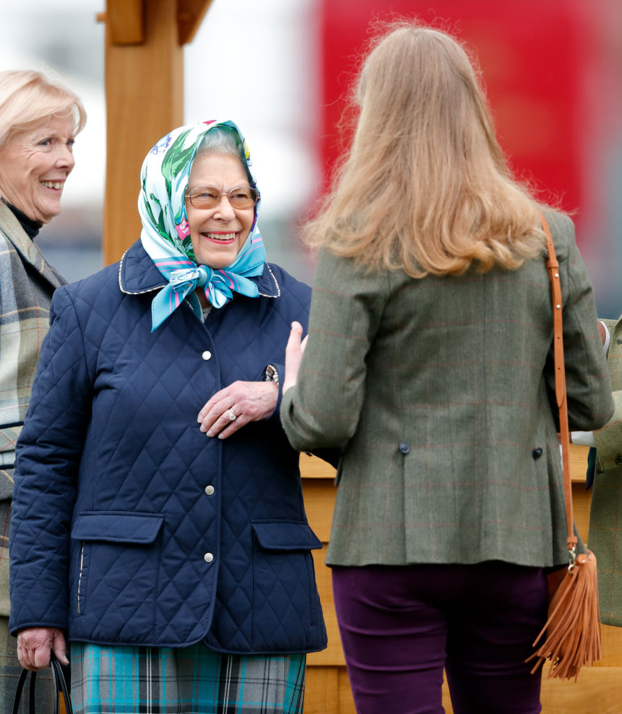 Rainha Elizabeth de frente para sua neta Louise, que está de costas para a foto